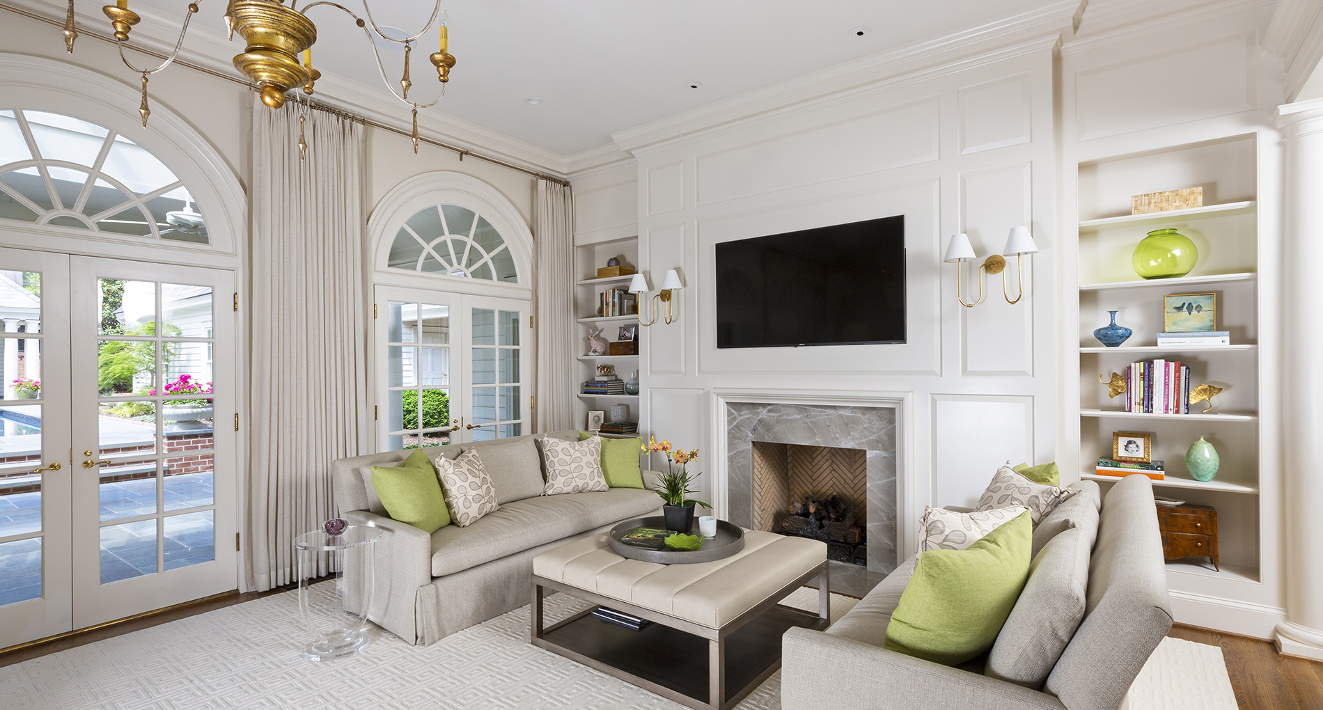Custom all neutral living space with green couch pillows and a fireplace