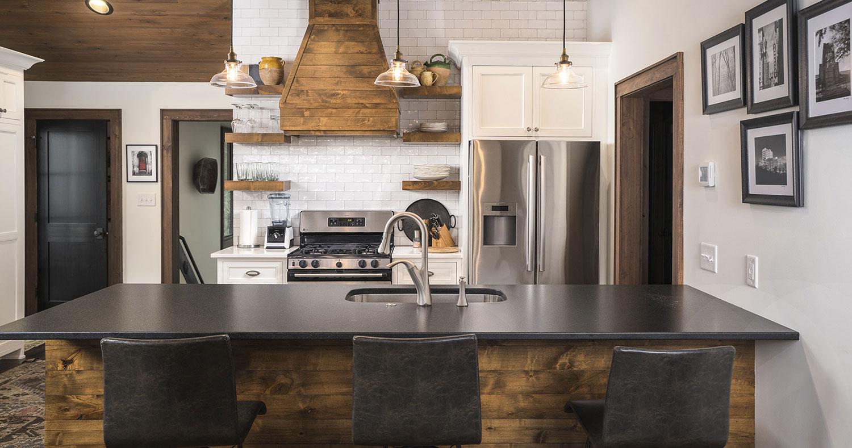 custom kitchen with white subway tile backsplash white cabinetry with black granite countertop and artisan wood finishing