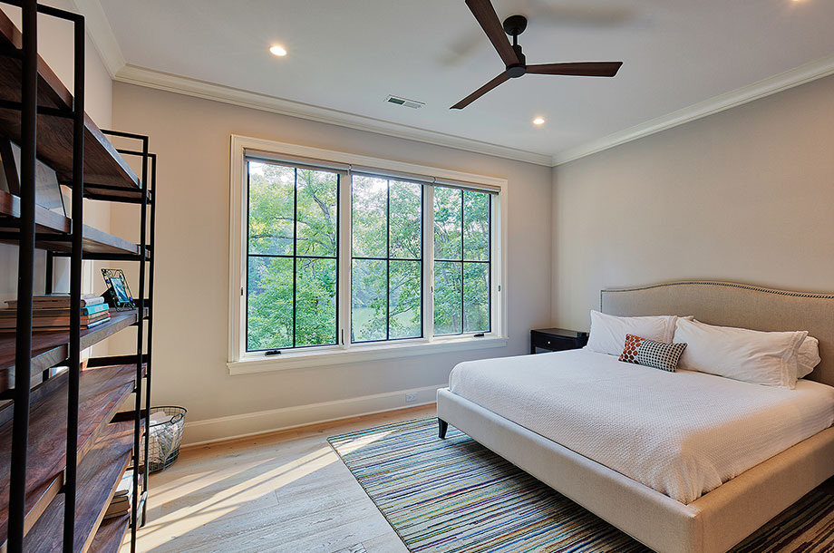 guest suite with large shelving unit against one wall and large windows