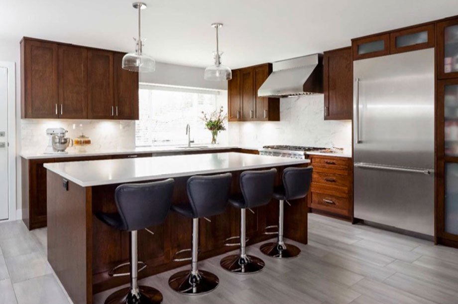 modern kitchen cherry wood with white countertops and stainless steel appliances