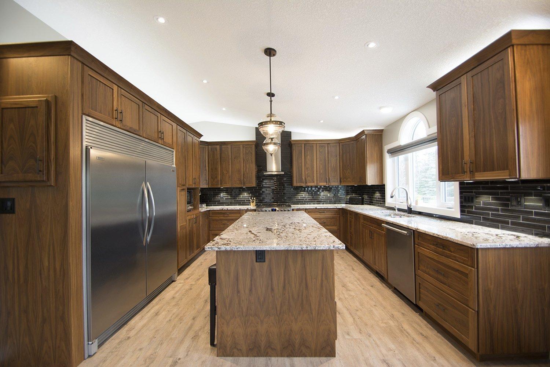 custom kitchen with natural wood finishing on cabinets and island with black tile backsplash