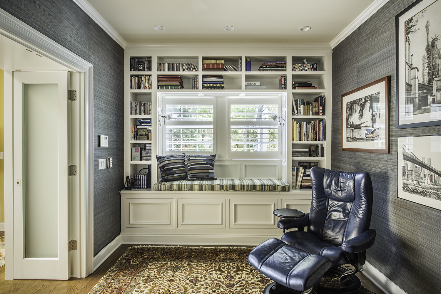 Custom reading nook with built in shelves around large window with seat inset