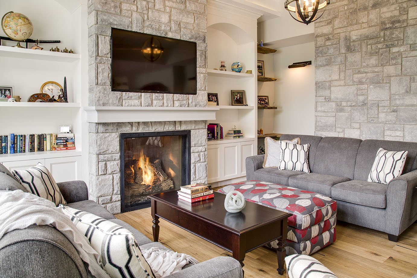 Cozy custom living space with burning stone fireplace built-in cabinetry and grey sofas