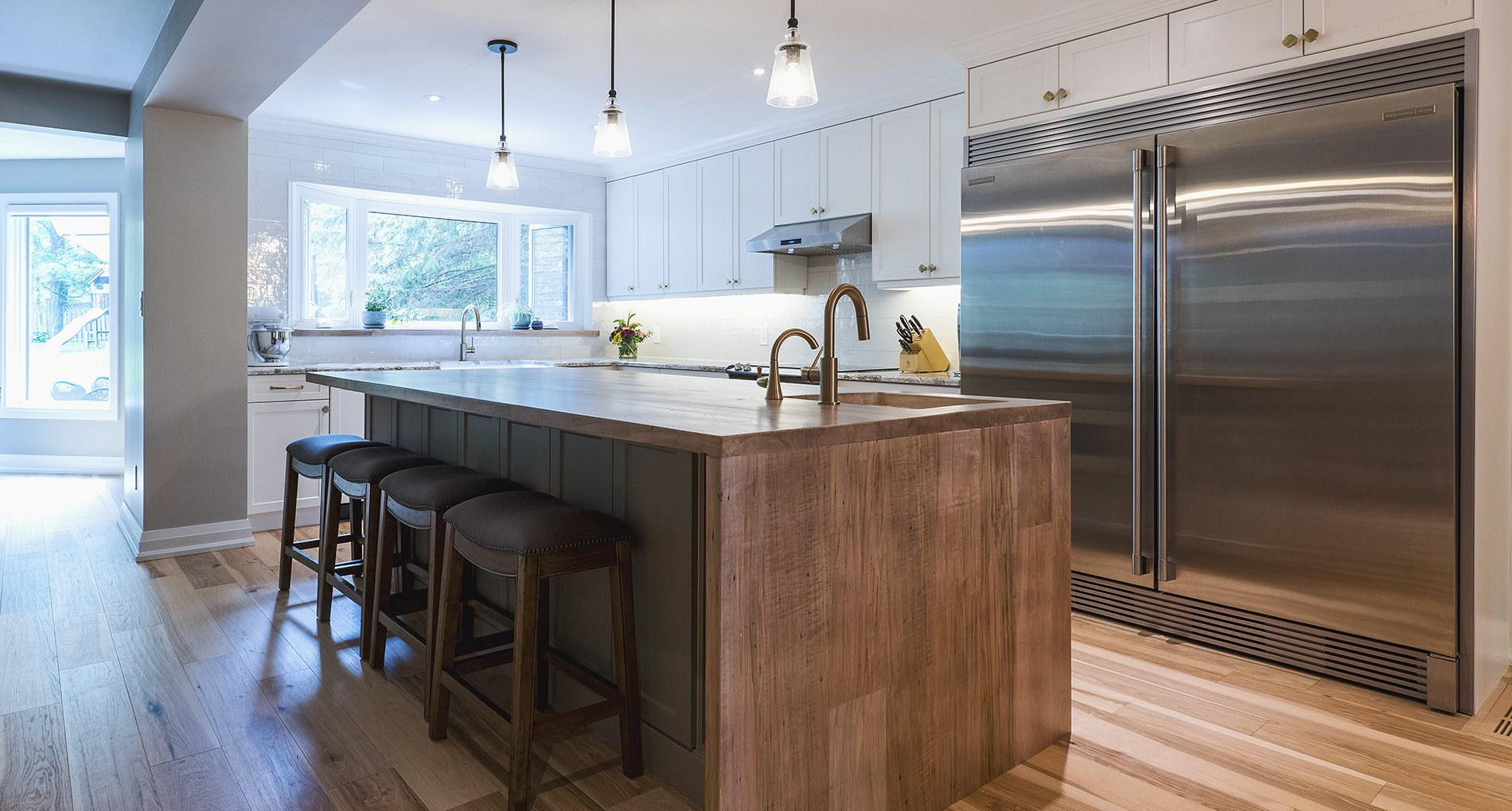 custom kitchen with large stainless steel fridge and large island with wood finishing