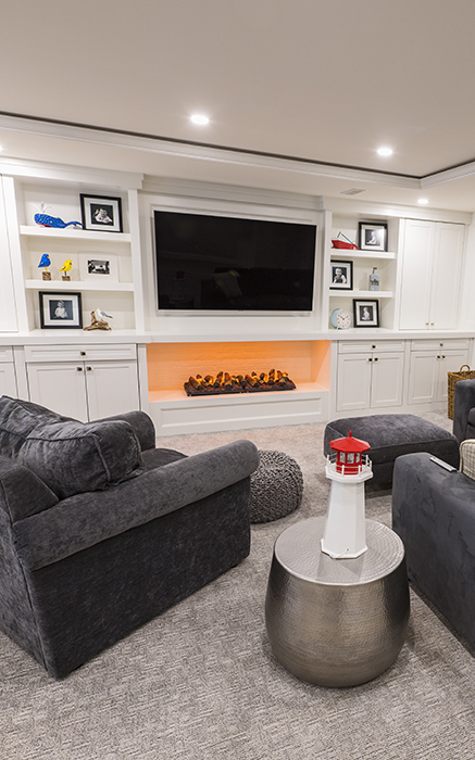 custom entertainment space with two lounge chairs around fireplace and tv