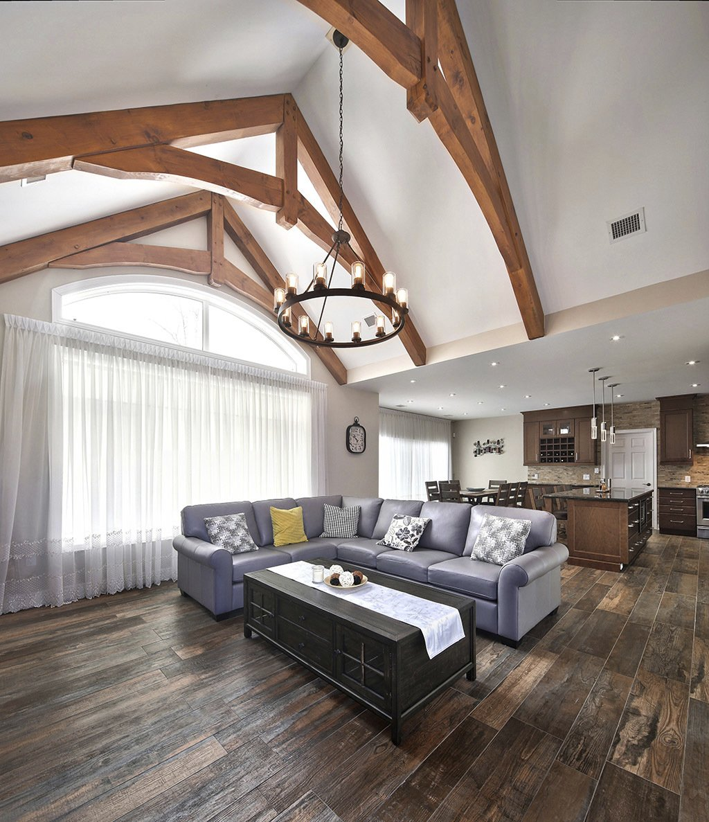 Custom Collingwood living space with high ceiling and large lighting fixture over grey sofa
