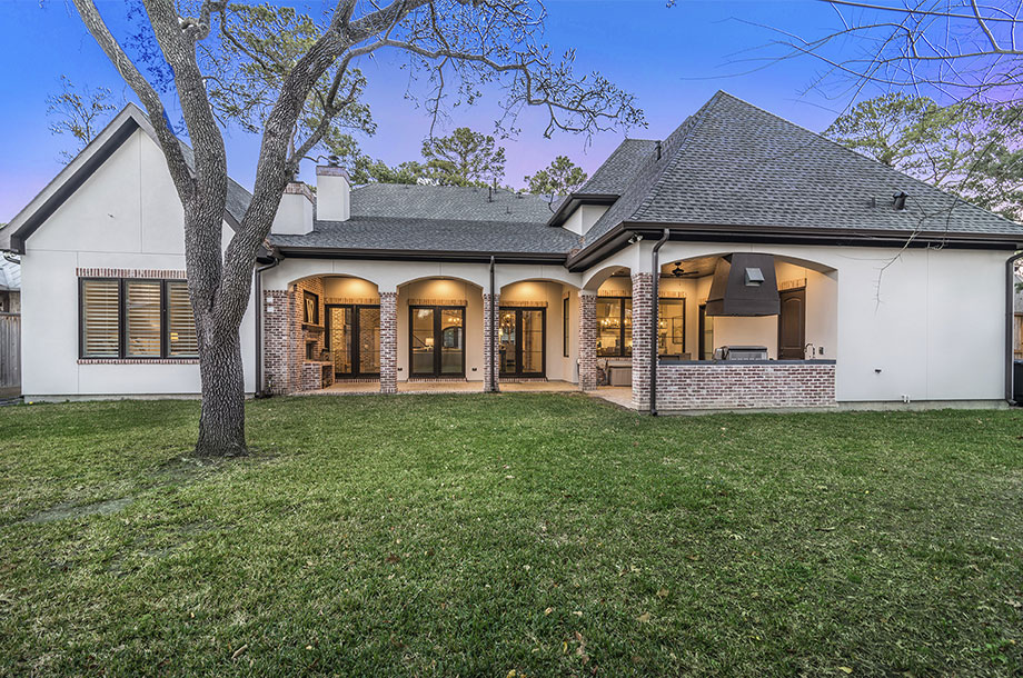 exterior of single story home with large tree planted amidst even lawn of turfgrass