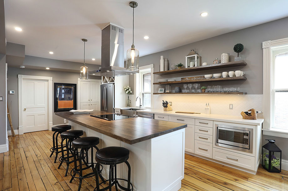 Kitchen Renovation with large island, white custom cabinetry, and stainless steel appliances