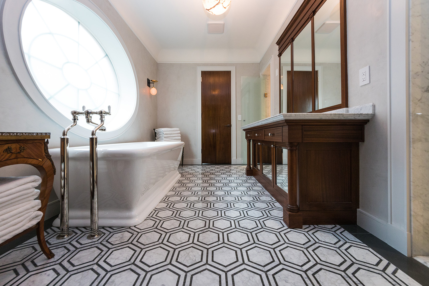 spa style bathroom with destination tub and hexagon patterned tile