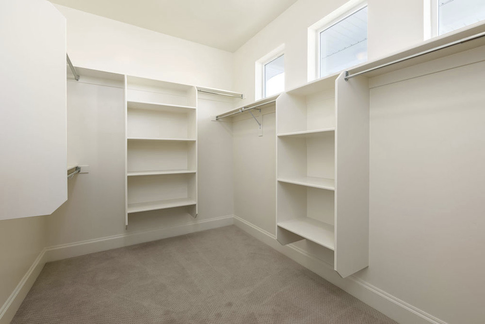 walk in closet with built in shelving and small windows