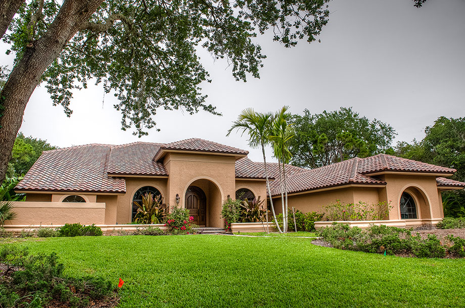 adobe style single story custom home surrounded by trees with healthy turfgrass front lawn