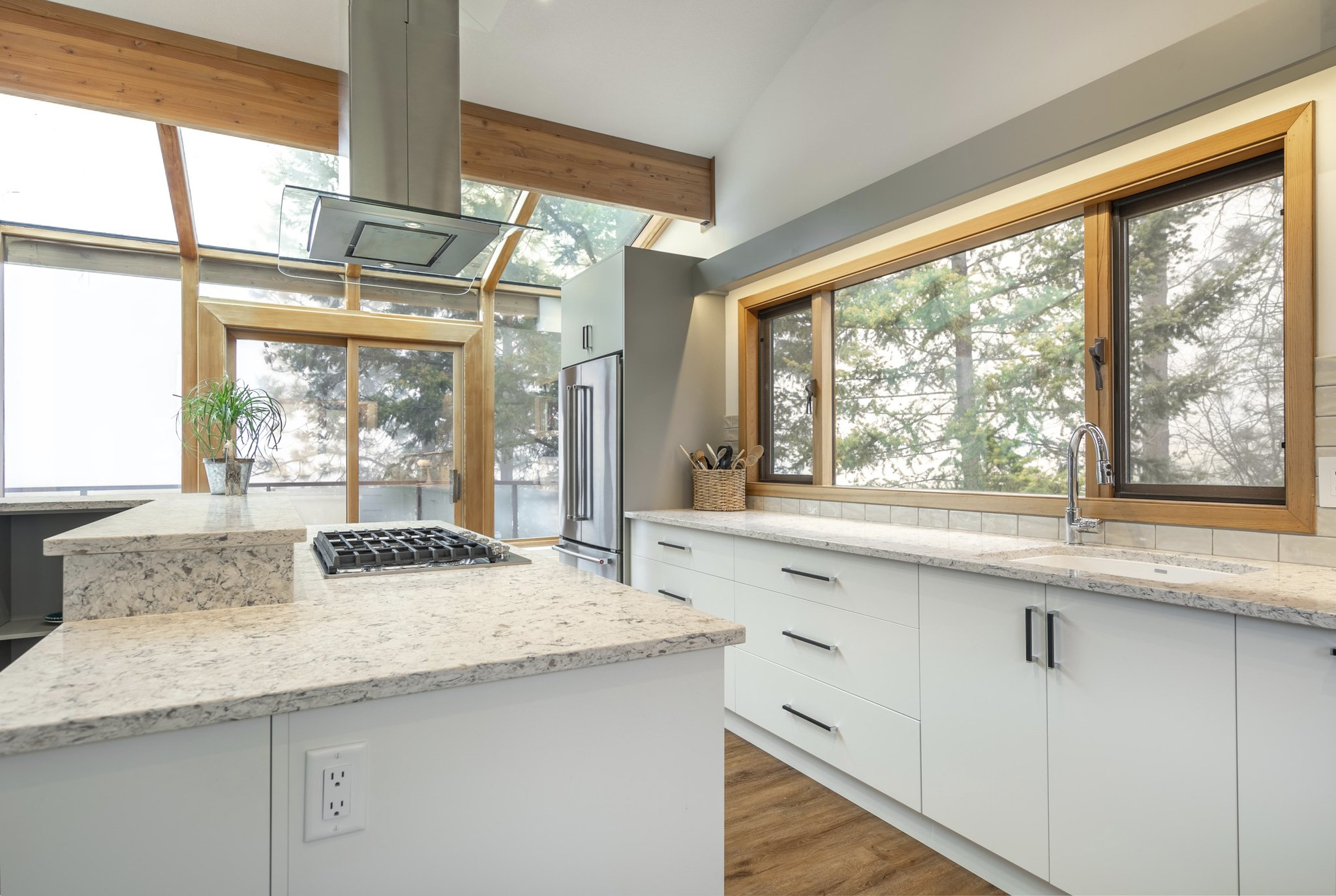 Kitchen all white cabinetry and large windows all over