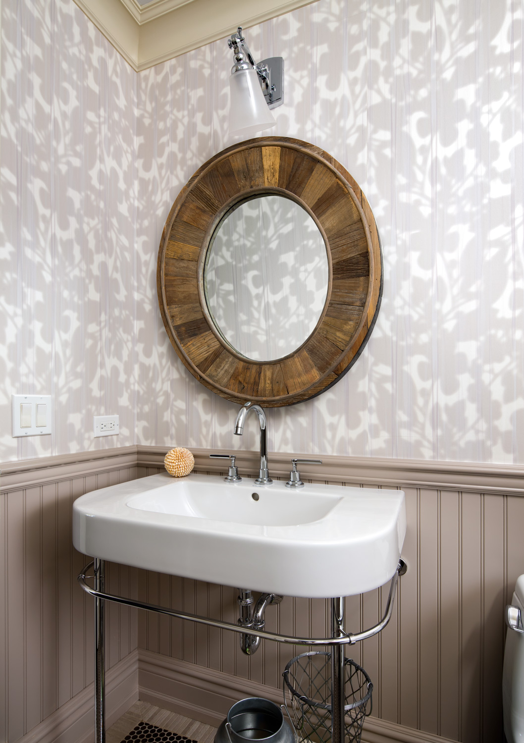 bathroom with subtly textured grey and white wallpaper and circular mirror with wood detailing