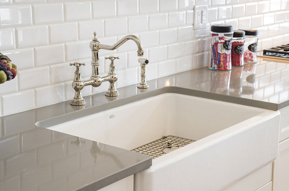 kitchen sink with rectangular white tiled backsplash and gold faucet