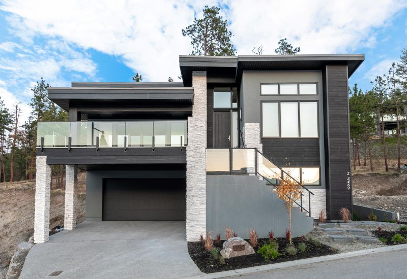 Modern home with dark flat roof and attached garage