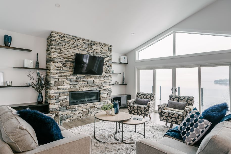 custom living room with stone fireplace and a lakeside view