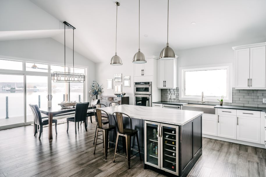 Kitchen with light walls, grey flooring, white cabinets and light dark island