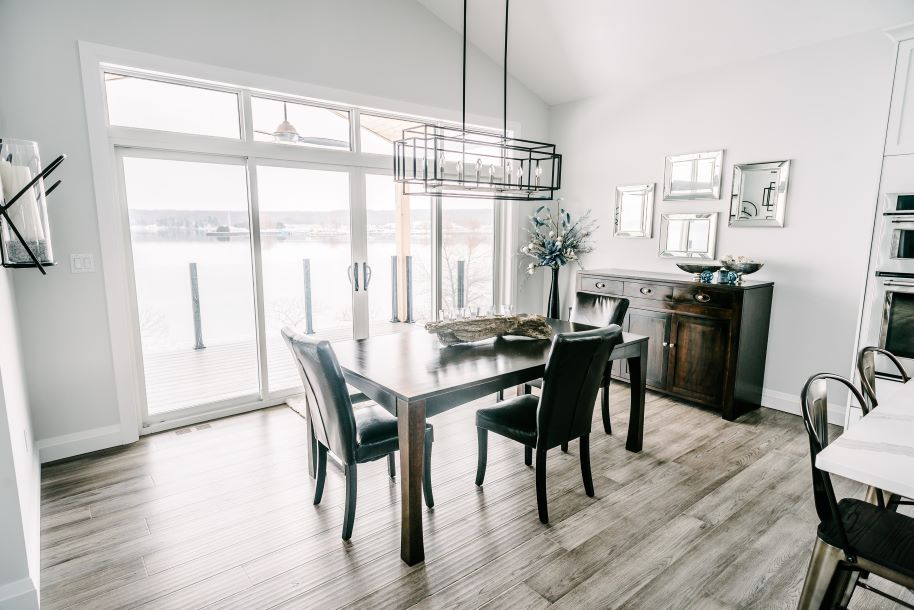 dining room with light walls, modern light fixture and view of the lake