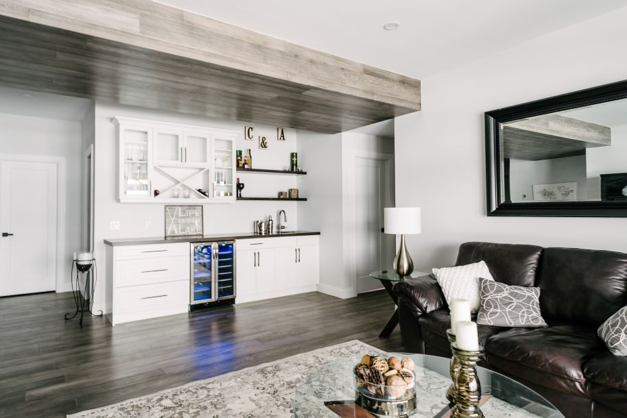 Kitchenette with wine cooler and custom white cabinets, light walls and neutral floors