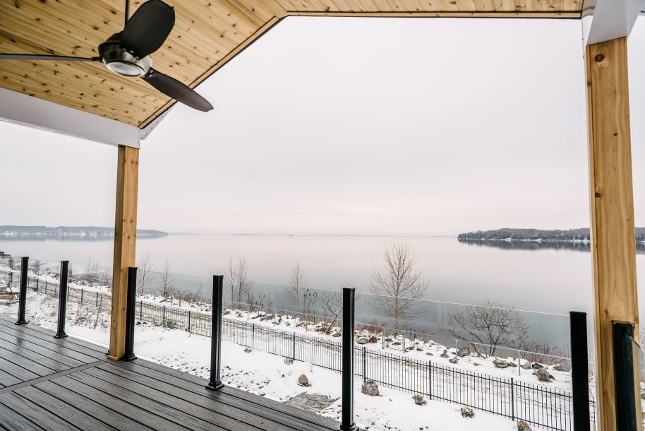 View of lake from a porch with dark outdoor fan