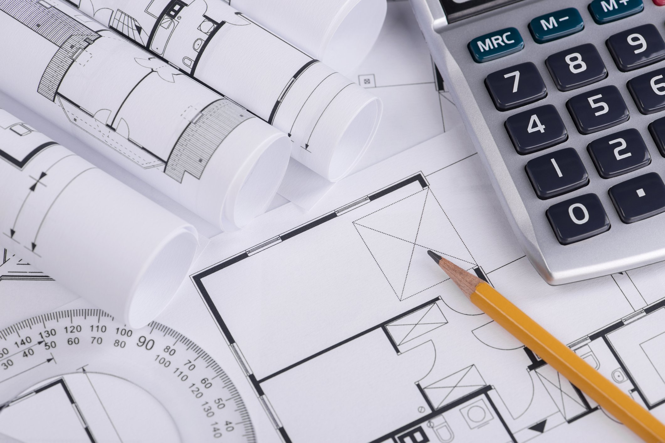 Home construction blueprints with calculator and pencil on top