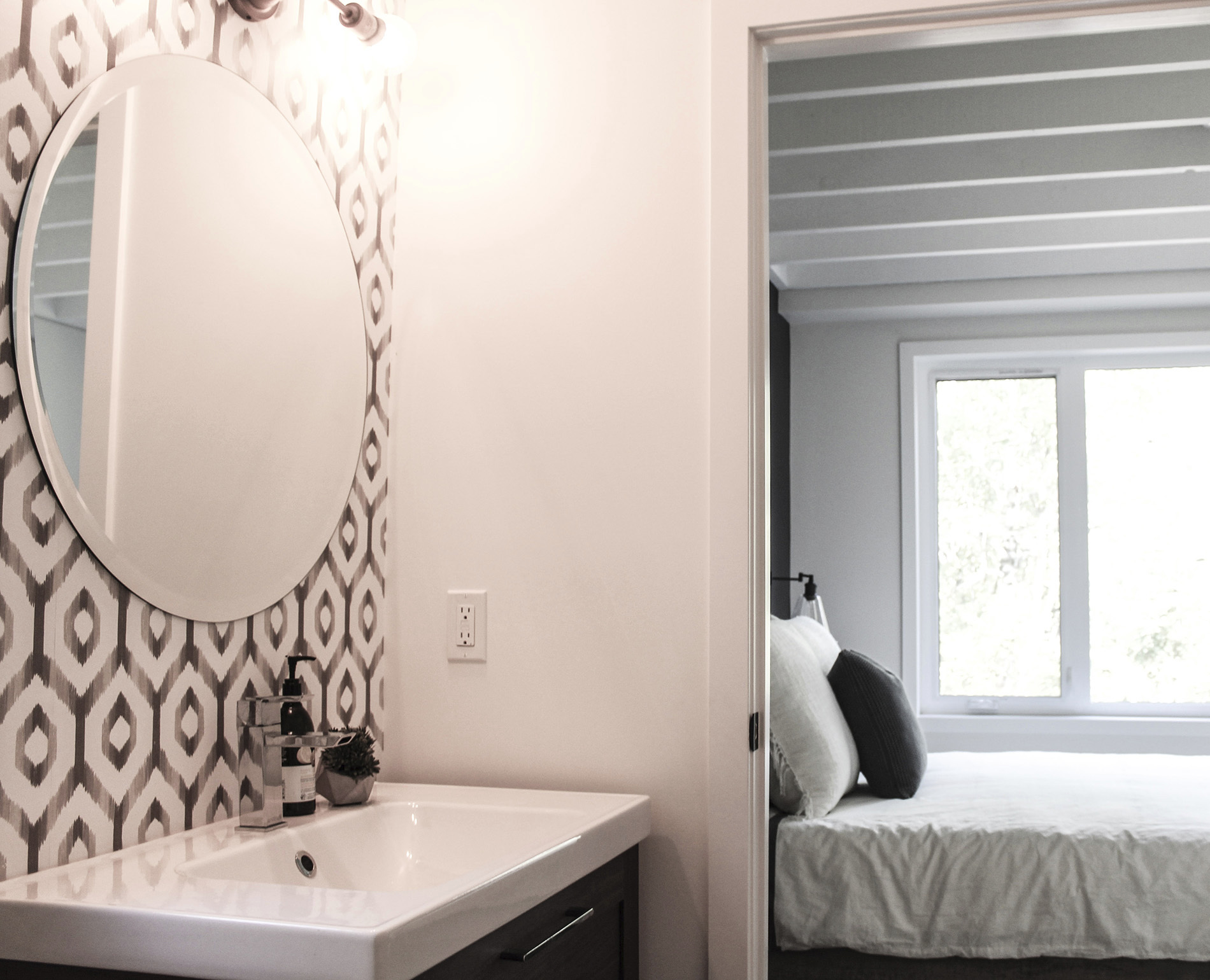 bathroom connected to guest room with patterned grey wallpaper