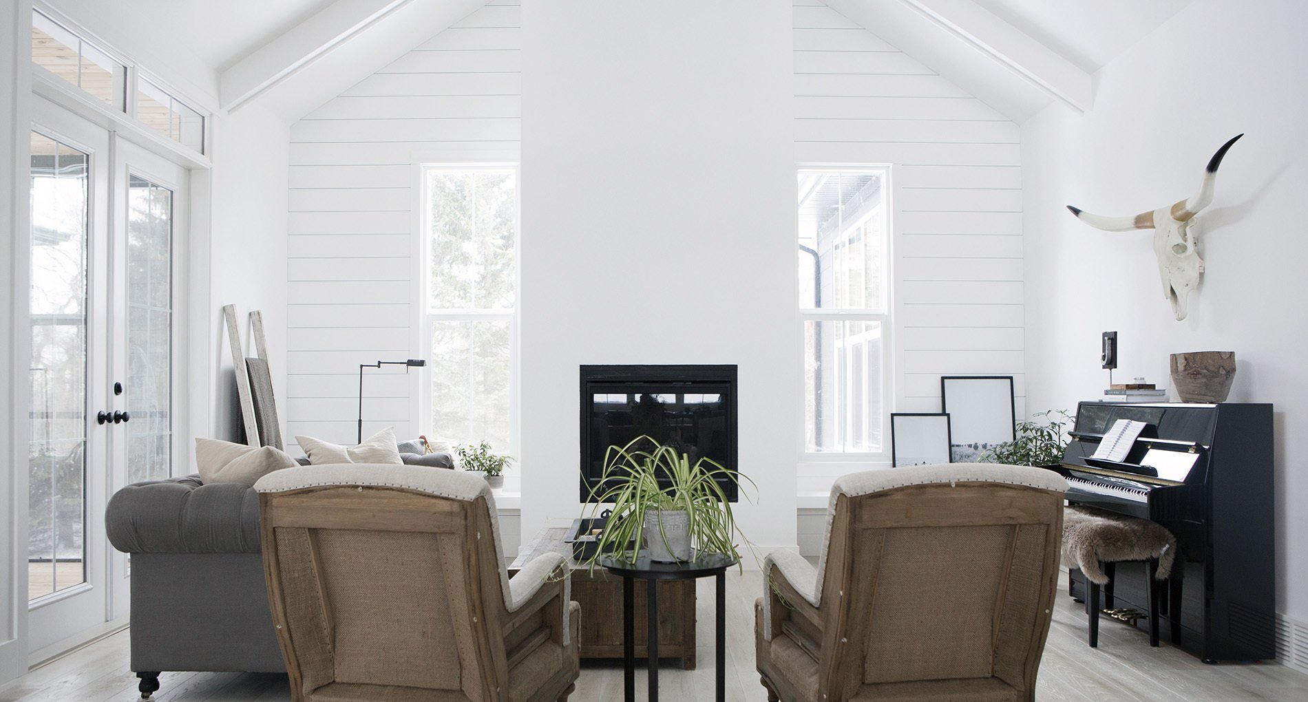all white modern living space with two light leather recliners with skull hanging above small piano