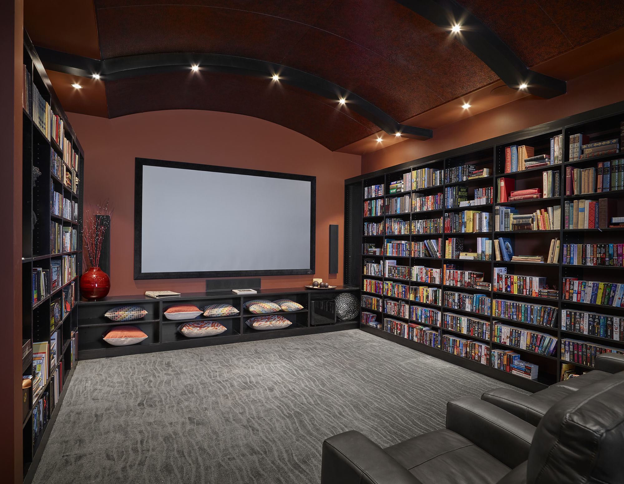 custom entertainment room with built in shelving large movie screen and recliners