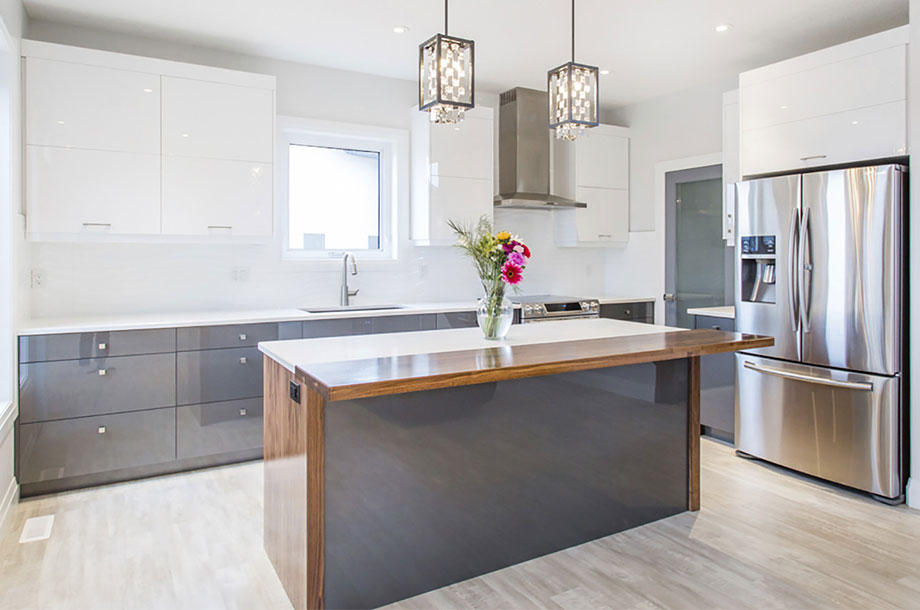 clean modern kitchen with glossy grey island and white counter tops and vase of roses at center