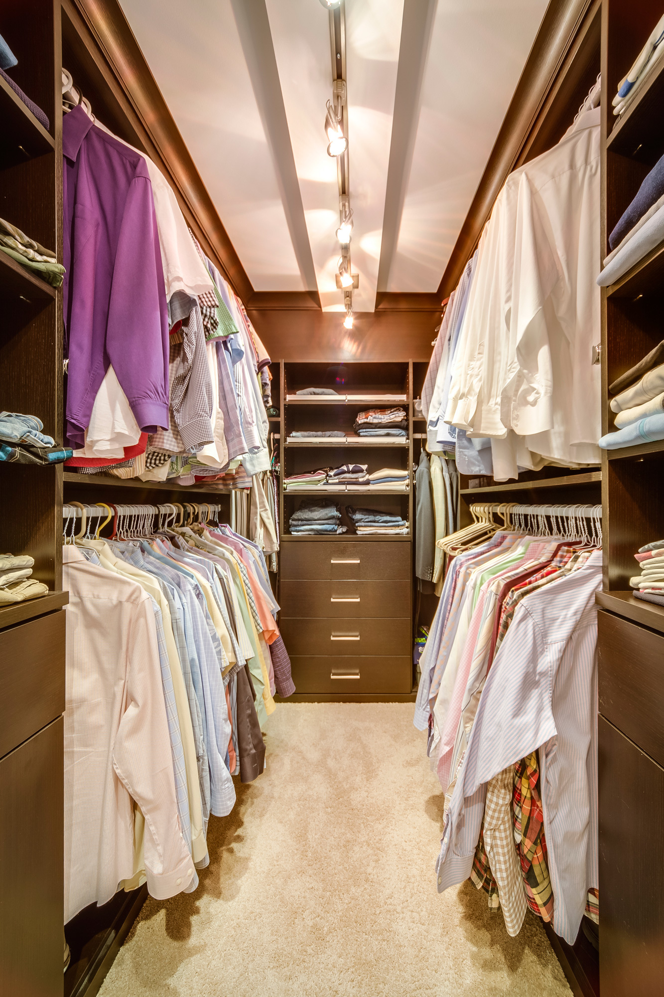 filled walk in closet with built in shelving and drawers and multilevel hangin rods