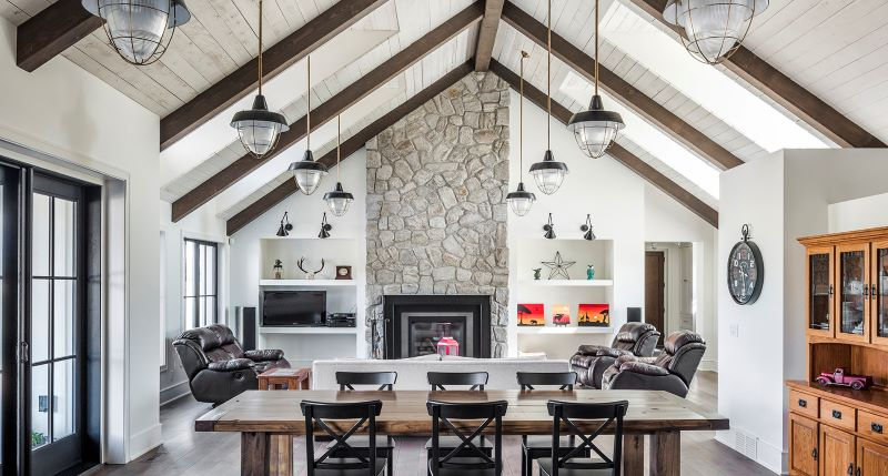 Dining room with light walls and stone fireplace with exposed beams