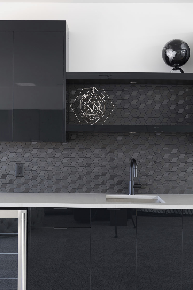 modern kitchen all sleek black appliances with white counters and black geometric patterned backsplash
