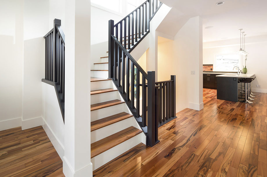 staircase with black banisters white walls luxury vinyl flooring