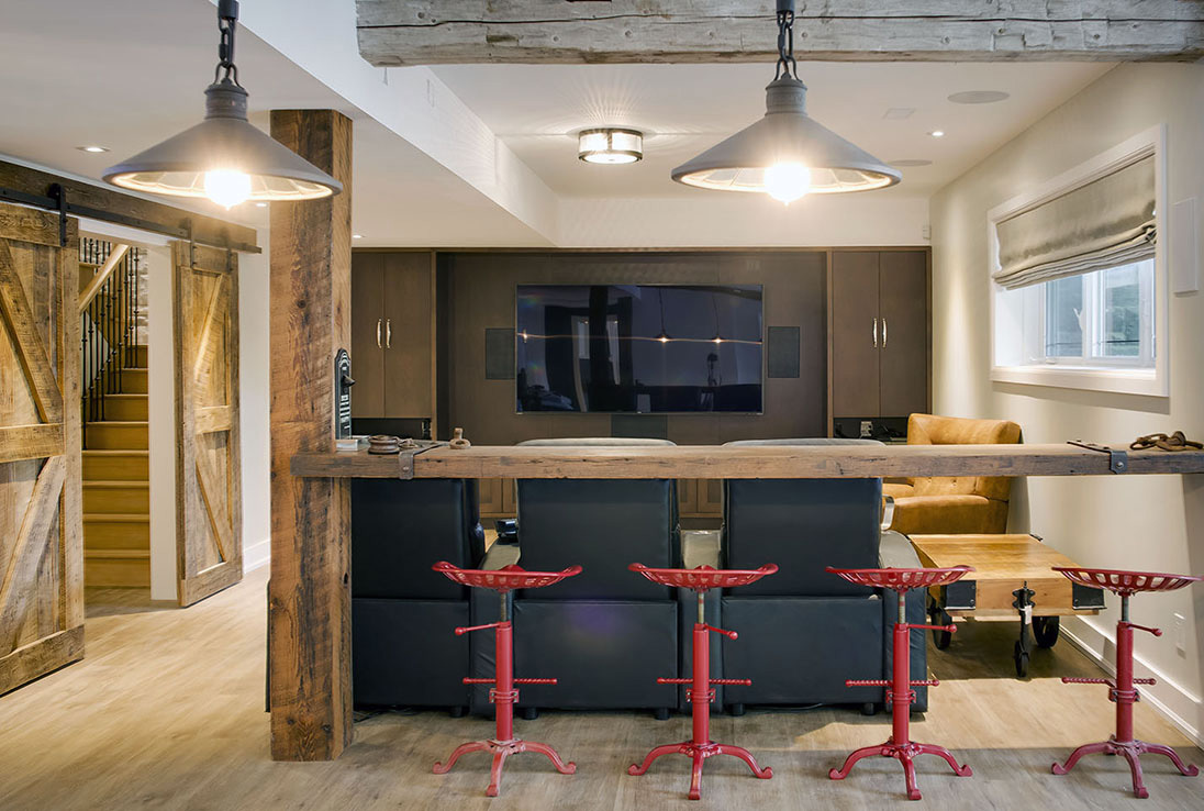 Custom basement entertainment studio with sliding wood barn doors and natural wood bar with red barstools