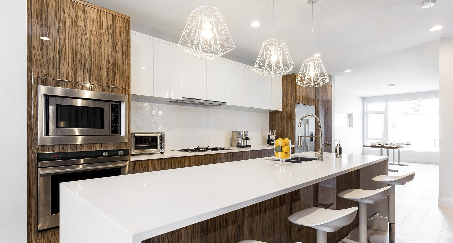 Kitchen with glossy white finishings and wood accents and custom white geometric overhead lighting fixtures.