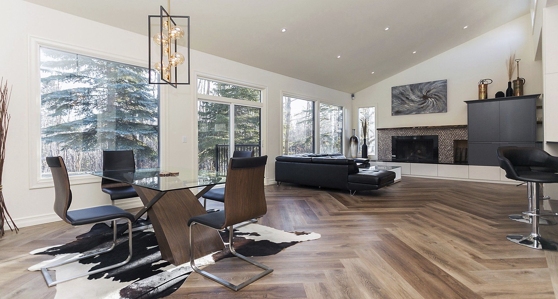 Modern custom living space with patterned wood flooring, a fireplace and big windows.