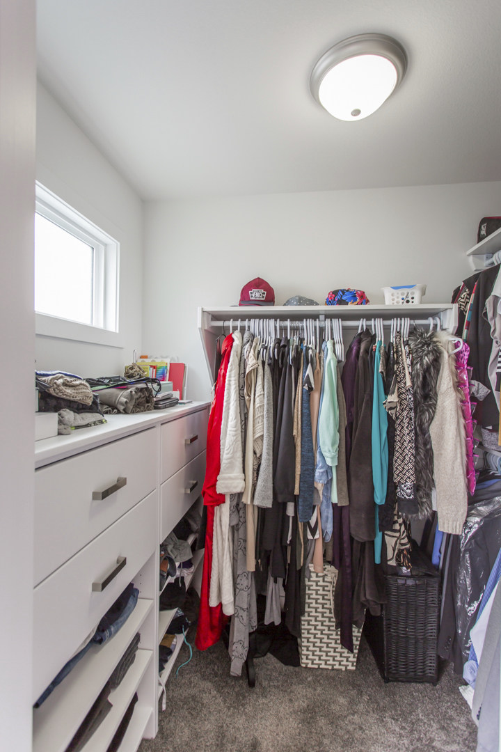 closet with wall of built in drawers and extra shelving