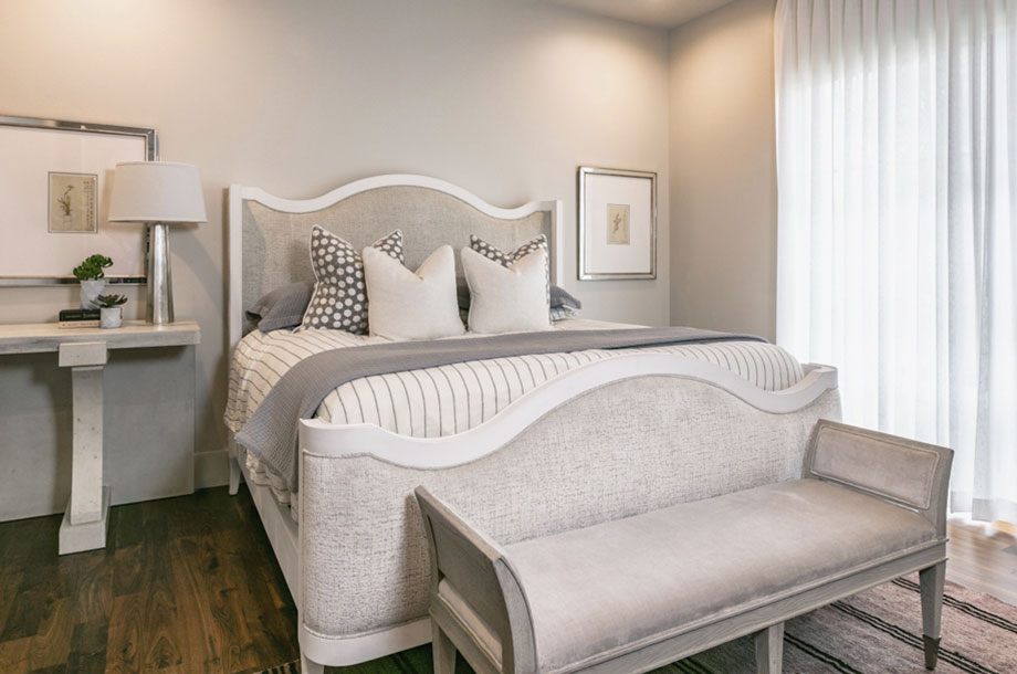 grey and white guest suite with small seat at the edge of bed and access to small patio