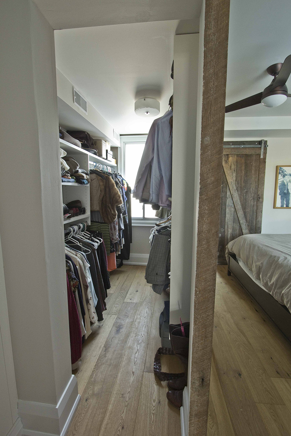 walk in closet with built in shelves for shoes on one side two hanging racks on the other