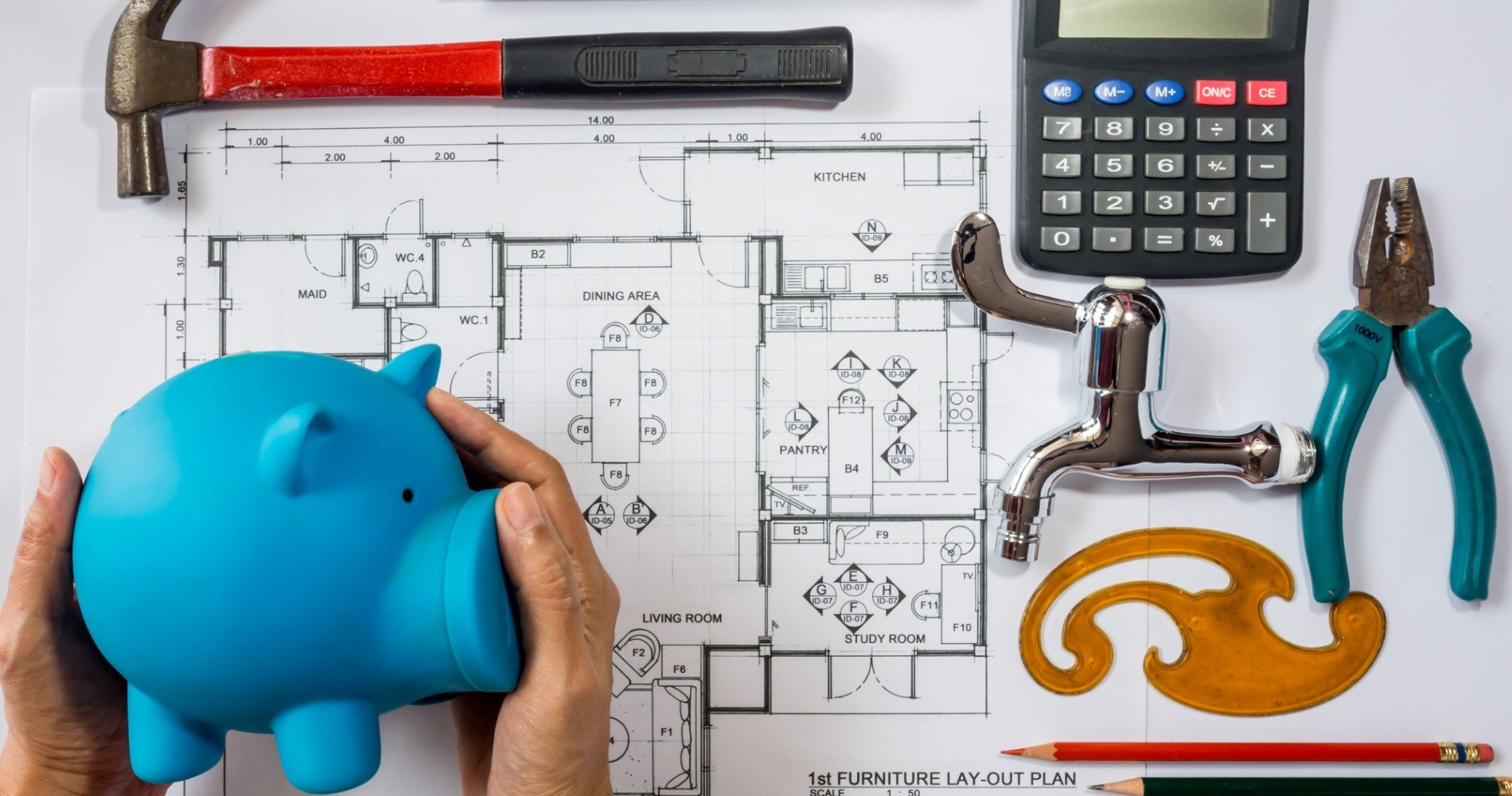 A person planning their budget over home blueprints
