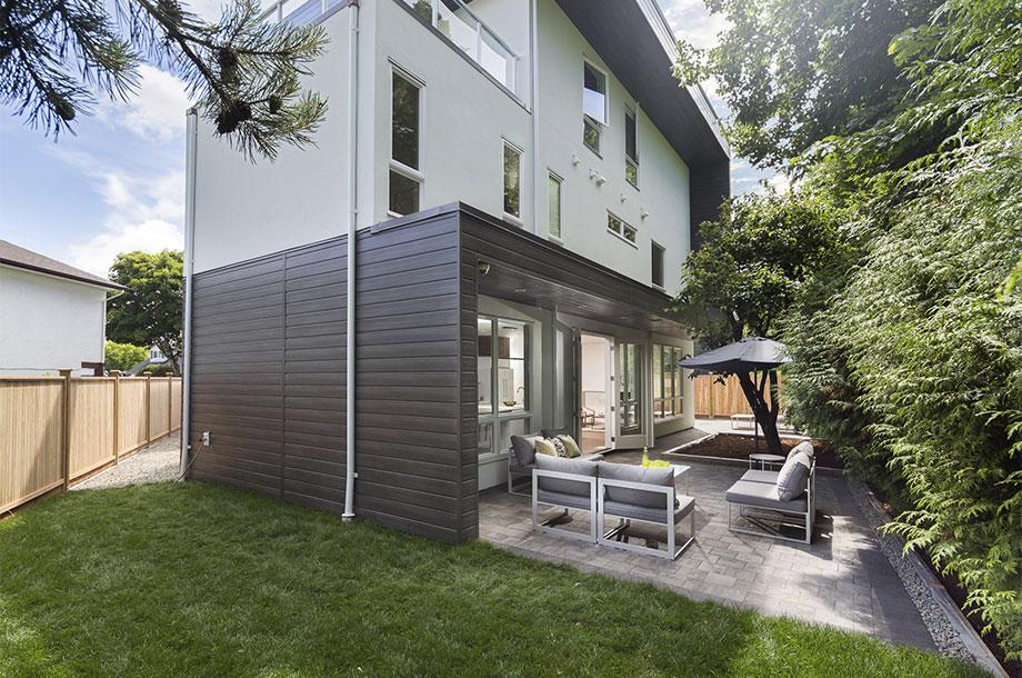 side of multistory custom home with turfgrass backyard