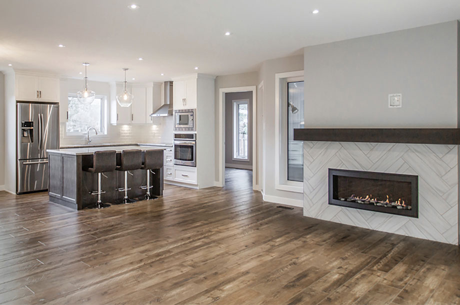 empty living area with modern fireplace and kitchen in background