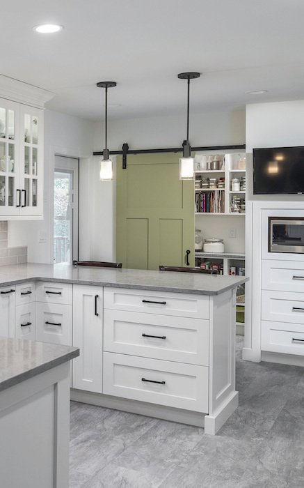 Custom kitchen with all white cabinetry and sliding jade green door to pantry.