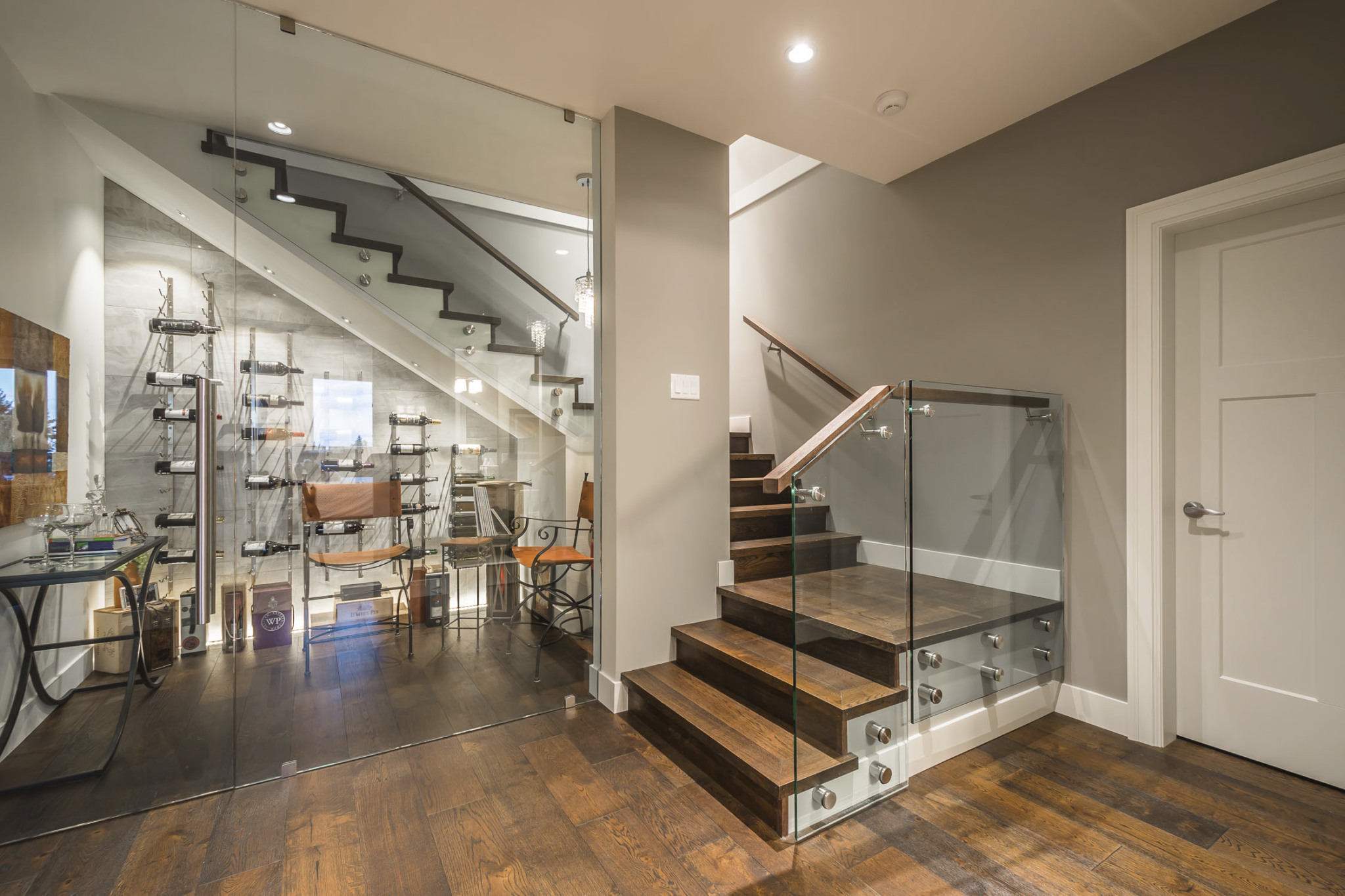 stairs leading down to glass wine cellar in basement
