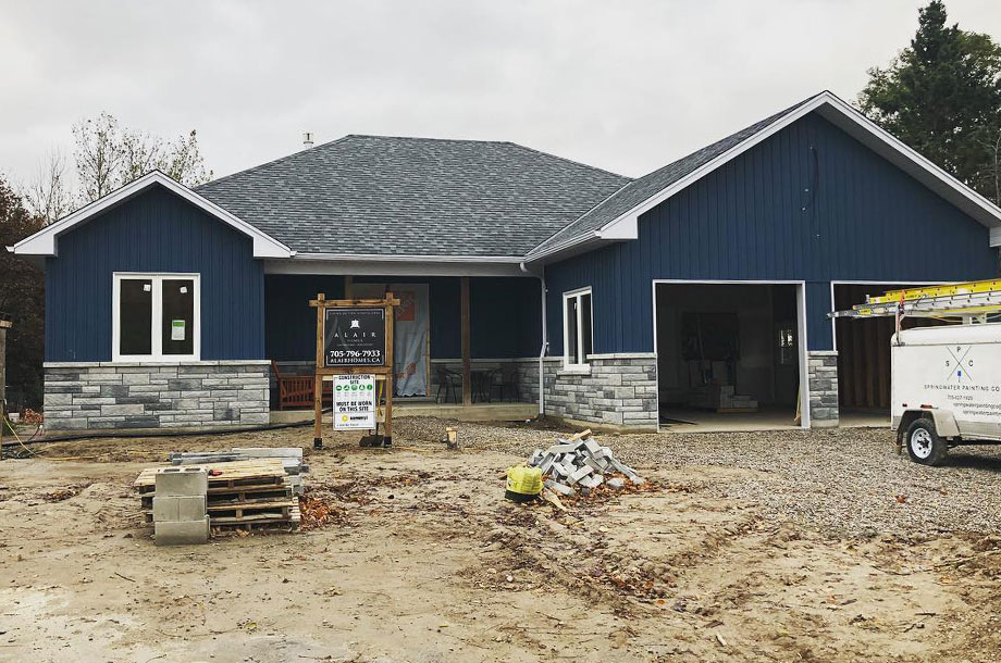 Custom home with navy vertical vinyl siding and custom masonry