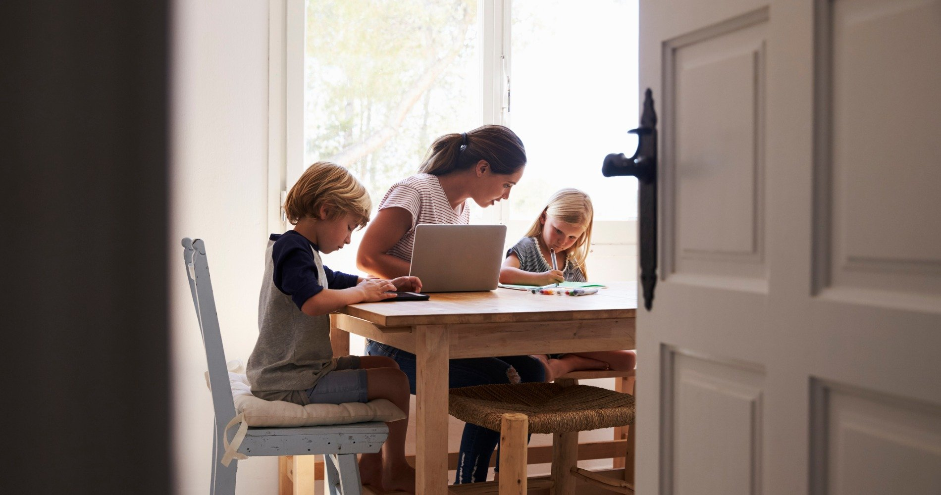 Family working on homework together at a kitchen table