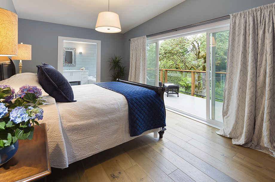 guest room with small patio light colored walls and wood floor