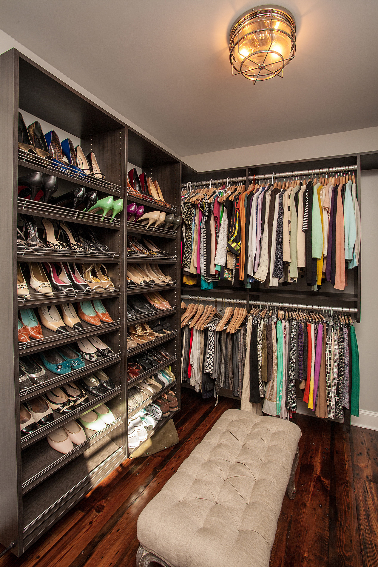 closet with built in shelves displaying shoes floor to ceiling with seat