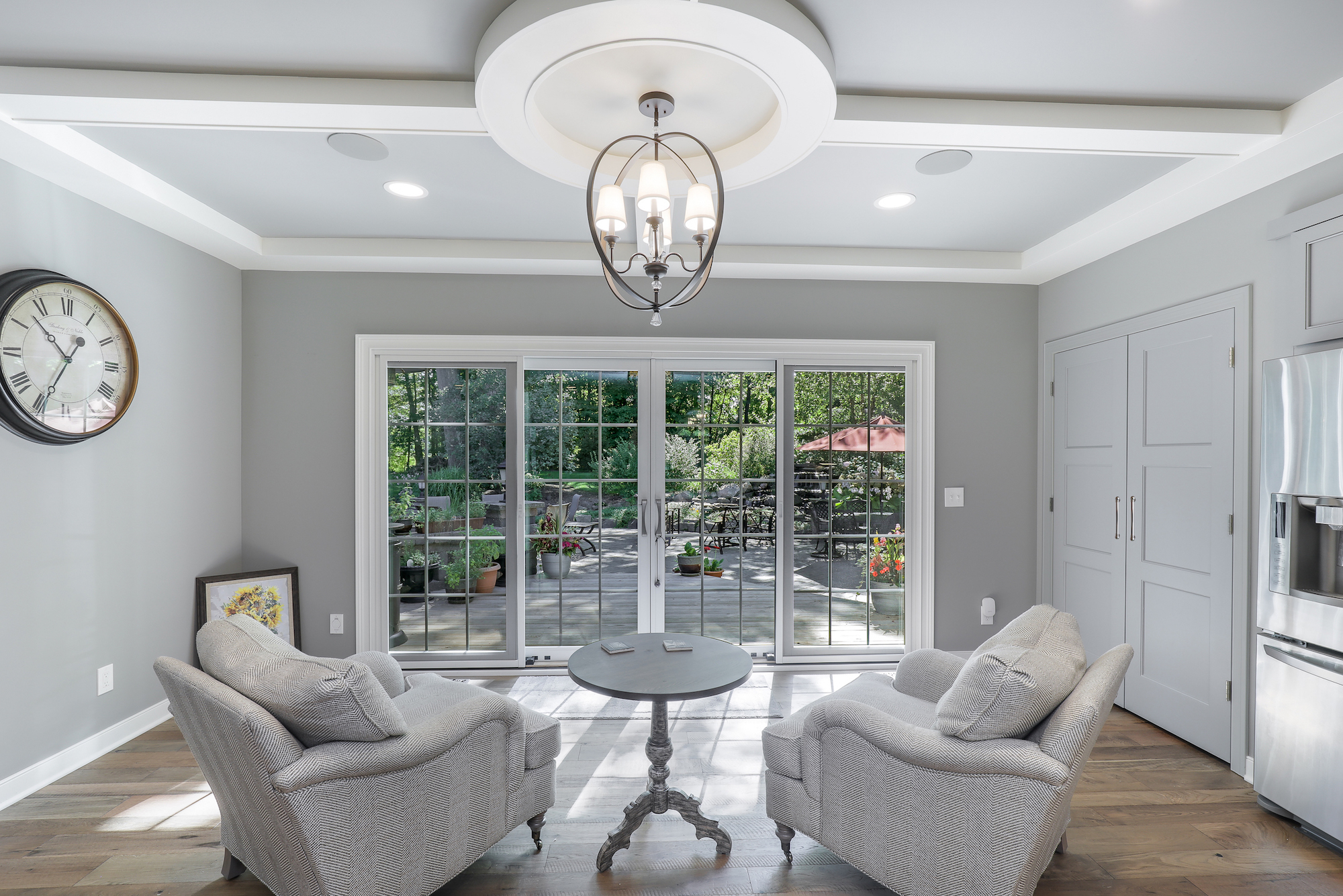sitting area of custom home with chairs facing outdoor area custom lighting fixture above