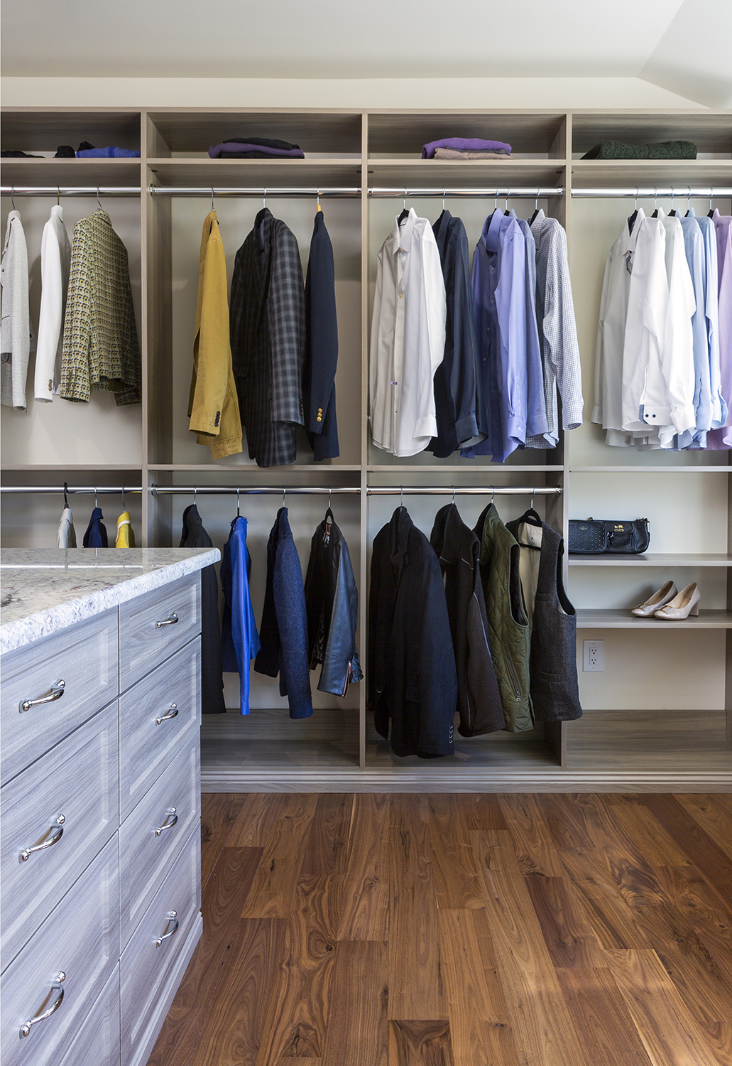 organized closet with island and mixed stain wood finishings
